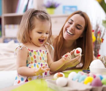 a happy kid marking the eggs with her teacher