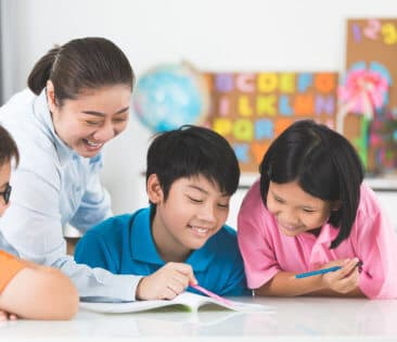 three kids laughing looking at a book with their teacher