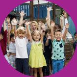 group of kids raising their hands with their teacher