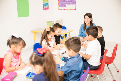 preschool teacher in a classroom full of students